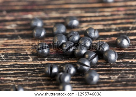 Lead sinker for fishing rods during fishing, close-up of round sinkers on a black board #1295746036
