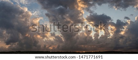 Leaden, storm clouds covered the sunset. Cumuliform cloudscape on blue sky. The terrain in southern Europe. Fantastic skies on the planet earth. Tragic gloomy sky. #1471771691