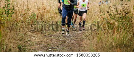 leader athlete runner in group of athletes run uphill trail