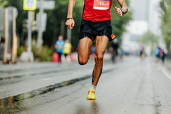 leader athlete runner running city marathon in rain