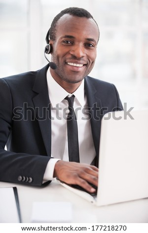 Leader of support team. Handsome young African man in formalwear and headset working on laptop and smiling at camera