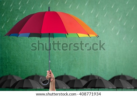 Leader person\'s hand holding rainbow umbrella distinctive unique among black color other on green school chalkboard background: Life-health Insurance protection, Business financial leadership concept