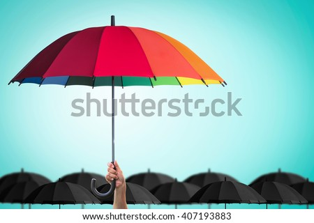 Leader person\'s hand holding rainbow umbrella distinctive unique among black color others on blue mint vintage sky background: Life-health Insurance protection, Business financial leadership concept