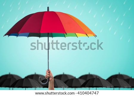 Leader person\'s hand holding rainbow umbrella distinctive unique among black color others on blue mint rainy sky background: Life health Insurance protection, Business financial leadership concept