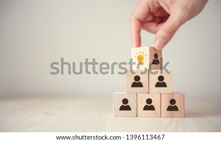 Leader with idea and innovation, Woman hand flips cube with icon light bulb and human symbol.