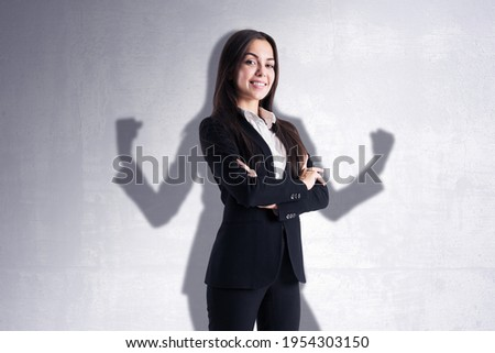 Leadership and power concept with confident businesswoman on her shadow background on light wall