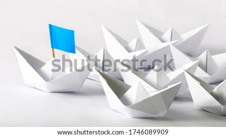Leadership concept. Blue flag Origami White Paper boat (ship) leading the others.  One leader ship leads other ships.  ストックフォト ©