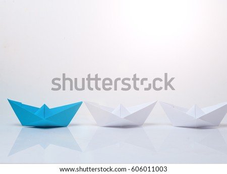 Leadership concept. Blue paper boat leading among white ships. Set of origami boats. Winner red paper ship on white background #606011003