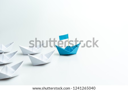 Leadership concept, blue paper ship leading among white on white background.