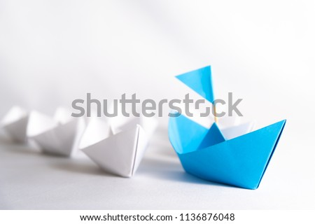 Leadership concept. blue paper ship with flag lead among white. One leader ship leads other ships. Stock photo ©