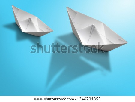 Leadership concept concept, paper ship with sailing boat shadow on blue