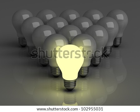 Leadership concept, One glowing light bulb standing in front of unlit incandescent bulbs with reflection on dark background