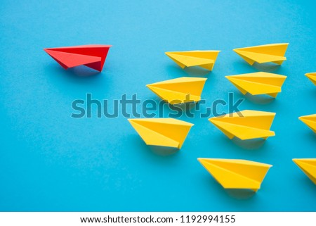 Leadership concept. Red paper plane origami leading among small yellow planes on blue background. Leadership skills need for top management in organization, company ex: supervisor, manager, CEO, CFO.