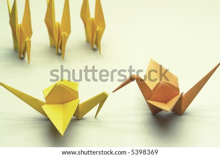 Leadership concept. The orange bird commands all the other birds.   In the Japan, Tsuru origami represents luck, peace, happiness and longevity.