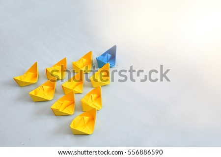 Leadership concept with paper boats on blue wooden background. One leader ship leads other ships. Filtered and toned image #556886590