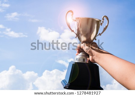 Leadership of champion trophy placed on hand raised holding for award of competition concept. Golden cup with blue sky ligt flare for highest achievement of sport or business. Success Awards concept #1278481927