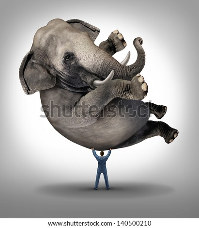 Leadership solutions business concept as a take charge businessman lifting an elephant as an icon of a leader with courage and determination to release the power within and achieve the impossible.