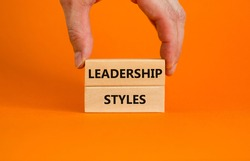 Leadership styles symbol. Wooden blocks with words 'Leadership styles' on beautiful orange background. Businessman hand. Business and Leadership styles concept. Copy space.