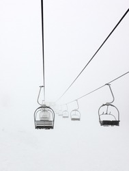 Leading lines of the cables on a 2 person chairlift in a ski resort show the fog on a winter day.