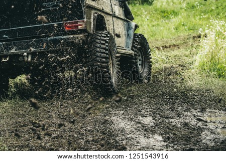 Leading up through the extreme trails. SUV or offroader on mud road. Car racing offroad. Offroad car in action. Dirty car drive on high speed. Car wheels on steppe terrain splashing with dirt. #1251543916