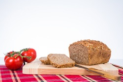 leaf of bread with tomatoes and knive as background