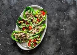 Leaf of mini roman salad stuffed with tuna, egg, tomato, avocado on a dark background, top view. Delicious appetizer, tapas, snack