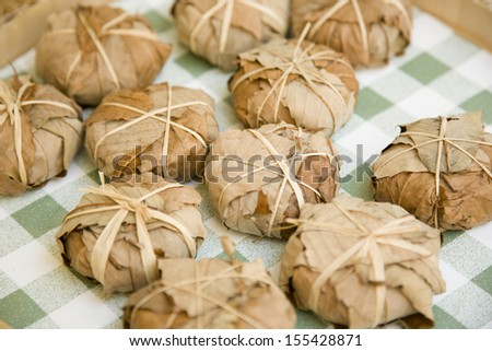 Leaf wrapped and bandaged cheese pieces at marketplace