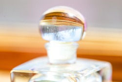 Leafless bare trees reflected in the top of a glass perfume bottle on a wood windown sill