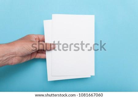 Leaflet A5 flyer mockup in man hand on blue background.