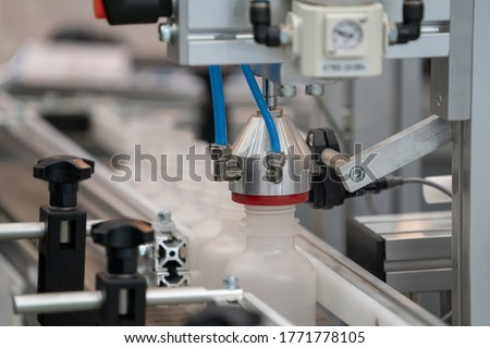 Leak tester for medicine bottles at line conveyor in pharmaceutical industry. Industrial Machine for quality of medical product in line conveyor processing. Industrial and factory technology concept. ストックフォト ©