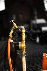 Leaking Fire Hydrant Spraying Water Closeup UK city hose yellow freeze time dark background isolated worker tap focus bokeh sharp object main