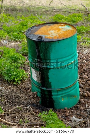 Leaking oil barrel left on a field