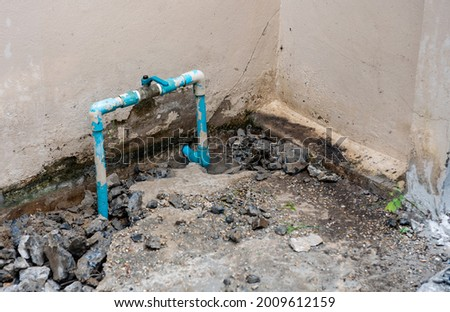 Leaking water pipe and water seeps from the water pipes outside the house. Fix and repair concept. Stok fotoğraf ©