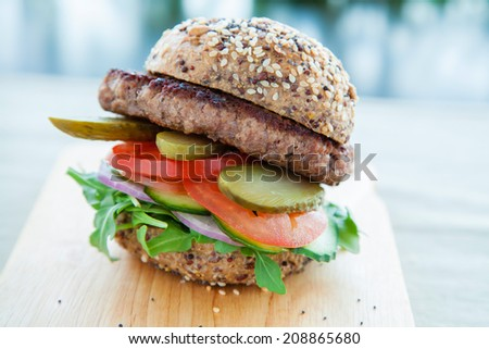 Lean beef burger with rocket pickles tomato and onions