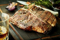 Lean healthy grilled t-bone steak with herbs and a sharp knife served on a wooden cutting board with a glass of whisky or brandy in a close up view