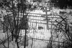 Leaning crosses and fences in the snow at the old cemetery. Black and white photo of graves. Gloomy mood. Cold winter weather. Shallow depth of field. Siberia, the Far North of Russia.