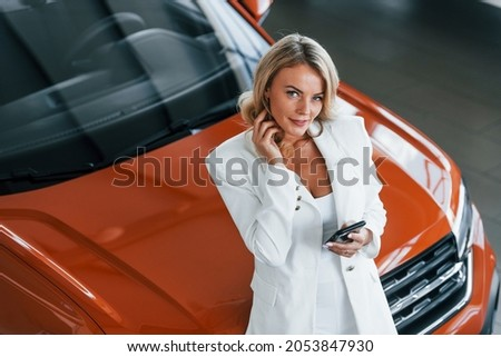 Leaning on the car. Woman in formal clothes is indoors in the autosalon.