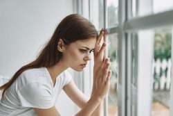 Leaning on the window, a woman looks at nature