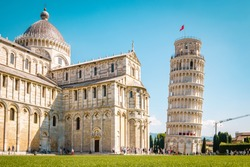 Leaning tower of Pisa, Italy with Basilica and Cathedral on a bright summer day with green gras low angle
