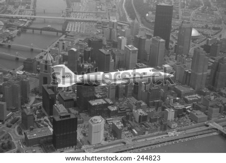 Learjet above Downtown Pittsburgh. - stock photo