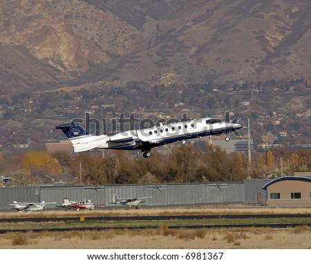 Learjet taking off from small runway gear down