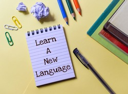 Learn A New Language. The text written in notepad placed on yellow background with notebooks, pen, color pencils and paper clips. Concept of joining educational programs and webinars, top view.