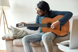 Learn and play. Young caucasian man sitting on sofa at home and adjusting acoustic guitar. Music school online. Distance education. Focus on man. Stay home, self isolation. E-learning