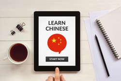 Learn Chinese concept on tablet screen with office objects on white wooden table.  Flat lay