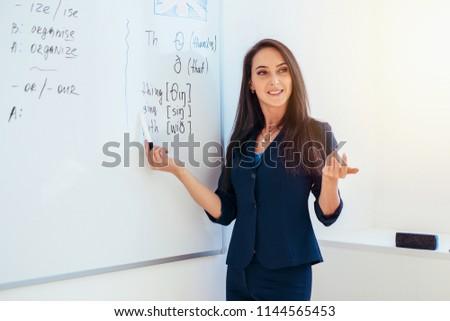 Learn english language. Teacher near whiteboard explains the rules.