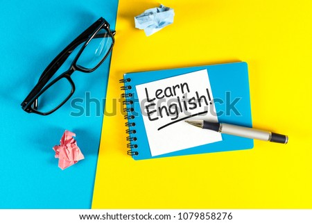 Learn english - note at blue and yellow background with teachers glasses #1079858276