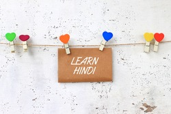 LEARN HINDI - concept words on paper with wooden clamps. rustic wooden background