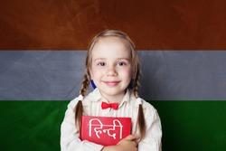 Learn hindi language. Smart child student on India flag background
