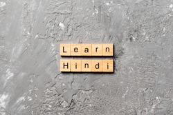 Learn Hindi word written on wood block. Learn Hindi text on table, concept.