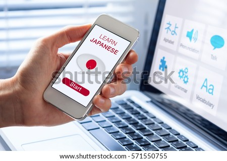 Learn Japanese language online concept with a person showing e-learning app on mobile phone with the flag of Japan #571550755